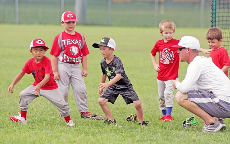 "Groesbeck head baseball coach Cameron Sellstrom, right, gives the ""go"" as a couple of youngsters take off during base running drills at the Teach Me More baseball camp held last week at the high school field. Photo by Stephen R. Farris/Journal Sports"